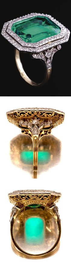 A very fine Belle Epoque emerald and diamond ring, circa 1910. The step-cut emerald weighing approximately 9.50 carats set within a double frame of circular-cut diamonds, highlighted by similarly-set shoulders, to a pierced scroll gallery.