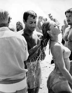 DON'T MAKE WAVES - Tony Curtis washes the hair of Sharon Tate between takes on the beach - MGM - Publicity Still.