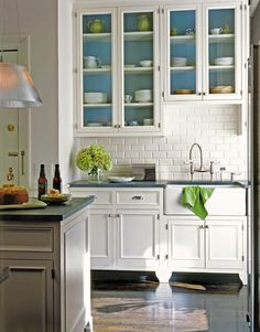 White kitchen cabinets with turquoise interiors and lime green accessories