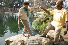 Portrait of senior couple stepping on rocks by lake in park Stock Photo