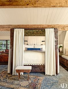 The master bedroom's Tara Design four-poster is crowned by a panel of vintage Ndop cloth from Cameroon and curtained in a Lee Jofa linen.