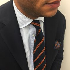Navy jacket, white shirt with light blue pin stripes, navy tie with orange stripes