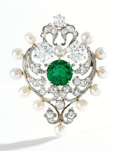 A Gold, Platinum, Emerald, Pearl and Diamond Brooch. Designed as a heart composed of scrollwork motifs, centering a round emerald weighing 2.82 carats, accented by two old European-cut diamonds weighing approximately 2.00 carats, further set with smaller old European and old mine-cut diamonds weighing approximately 1.00 carat, framed by 12 pearls. Signed Marcus & Co., fitted with retractable pendant loop, circa 1900.