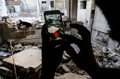 Here are the most influential, striking, and beautiful pictures from 2016. A Syrian gamer uses the Pokémon Go app on his mobile phone to catch a Squirtle amid the rubble in the besieged, rebel-controlled town of Douma, a flashpoint east of the capital Damascus, on July 23.