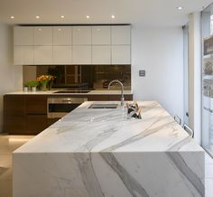Stunning Carrera marble bespoke kitchen island with inset ice trough in Roundhouse Notting Hill  showroom