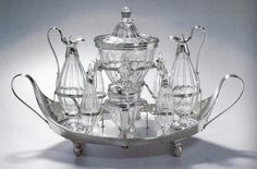 Silver or Sheffield-plate cruet stands, filled with elegant cut-glass bottles, were used on fashionable dining tables in the late 18th century.