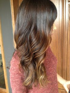 Long brunette curls with face framing caramel balayage highlights and bangs.