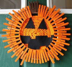 Halloween Wreath - Jack-o-lantern wreath - Pumpkin Wreath - Halloween Pumpkin - Crocheted Wreath -Clothespin Wreath  This fun little guy is a Halloween Wreath Jack O Lantern, sure to bring a festive Halloween touch to your front door. This is a twist on a clothespin wreath with the center made from hand crocheted yarn and felted eyes and mouth. Wreath is approximately 17x17. Includes hidden hanging wire.  Looking for something custom? Please let me know! I am happy to work with you to create…