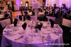 View of table setting at The Mirage Banquets in Schiller Park. White table cloth, black napkins, tall sparkle vase topped with white flowers. Photographed by The Wedding Studio, Schaumburg IL