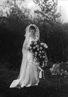 1920 bride. [Pretty veil and headpiece. Her gown is a good style too--in fact I can imagine someone wearing it today. I like the cowl neckline, the sleeves, and the interest at the shoulders--not sure whether those are some kind of trim, or brooches, or what.]