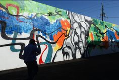 Man walks past a mural created by artist Emo on a building along Harrison Street.