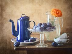 http://nikolay-panov.pixels.com/products/blue-teapot-and-damsons-nikolay-panov-art-print.html  • Rustic still life photography with blue vintage teapot, vase of fresh damsons and plums, and yellow orange flower in glass pitcher with water in kitchen in day light in summer