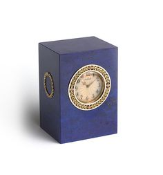 A gold-mounted lapis lazuli clock by Fabergé, fashioned from a single block of lapis lazuli, the top with a wreath of yellow gold laurels secured with red gold festoons within two bands of opaque white enamel, the dial enameled opalescent oyster over a sunburst guillochage beneath, with recessed silver gilt base containing the original gold key, the sides with red and green gold laurel wreaths. Workmaster: Henrik Wigström, St. Petersburg, circa 1908-1917.