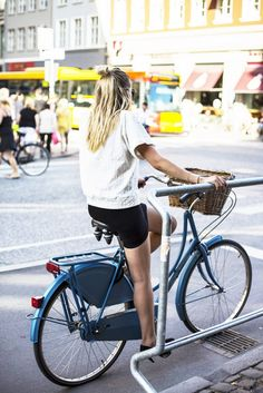 Girl riding a bike through the streets of Copenhagen, Denmark