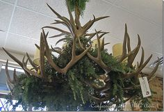 a faux antler chandelier decorated with natural greenery…