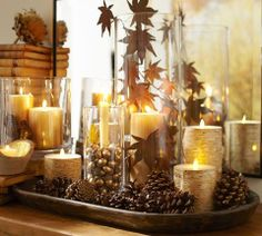No Link... just instructions! Create a gorgeous harvest mantle in just 3 easy steps:  1. Place flameless candles in glass vessels of varying heights. 2. Fill glass with faux or real acorns and leaves. (Spray paint gold for a gilded touch!) 3. Set candles in trays with pinecones to complete the look.