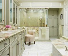 A serene, muted green palette, opulent materials, and top-notch amenities, including dual showerheads, a makeup vanity, and a floor-to-ceiling linen cabinet, treat the residents of this spacious master bathroom like royalty.