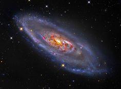 Galáxia em espiral com um centro curioso  O que está acontecendo no centro da galáxima M106? What's happening at the center of spiral galaxy M106? Os jatos de gás de temperatura diferente imprimem um conjunto de cores e formatos diferentes ao conjunto de estrelas.