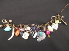 COST: £12.00!    This a handmade scrabble charm bracelet which has been made from 2 scrabble pieces, heart charms, glass beads, butterfly charms, plastic beads, a brass key, and more!    Total length: 8.5 inches/21.5cm approx. (length does not include extension chain)
