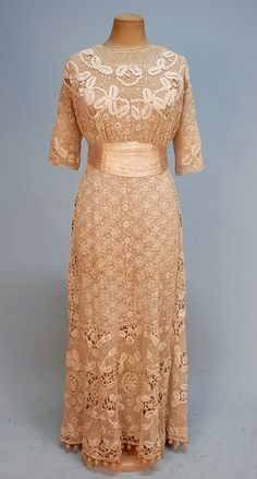 IRISH CROCHETED DRESS,   c. 1910.   1-piece short sleeve cream crocheted over cotton net, empire bodice with back hook and eye closure and boned satin cummerbund with bow, central floral panel flanked by bands of larger floral motifs, skirt having center panel with smaller scale floral, ball fringe at hem, under-dress having double hem ruffle. B-34, W-24, L-53.
