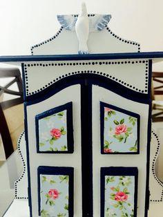 Oratório pintando em branco e azul, revestido de tecido floral.
