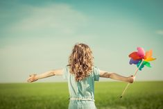 Happy child in spring field. Young girl relax outdoors. Freedom concept