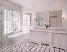 Gorgeous white bathroom with classic black/white tile great tub & huge glass enclosed shower...