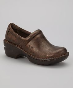 Fashioned with a brushed, faux leather finish and artfully stitched along the edge, this sturdy clog flaunts classic style. The platform traction sole provides durable support with every step, while a cushioned footbed ensures day-long comfort.
