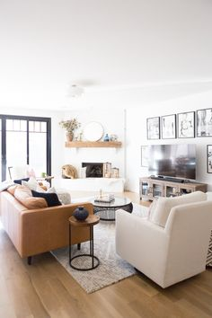 Tulsa Remodel Reveal Modern White Farmhouse black windows and doors modern leather sofa article Sven sofa white brick fireplace wood beam mantle round gold mirror tv gallery wall-1