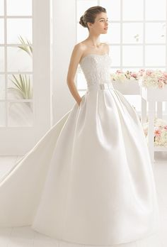 Aire Barcelona. Ball gown in beaded guipure lace bodice with a full mikado skirt and ribbon sash at the waist.