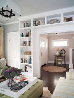 A Defined Entry:: To create a more defined entryway, the homeowners tucked a slim table behind the open door. The table adds display space for small accessories and provides a pleasing view through the living room's wide doorway.  Large built-ins define the doorway between the living room and entryway and display vases, books, and family photos.