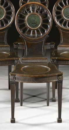 A SET OF FOUR GEORGE III MAHOGANY AND PAINTED HALL CHAIRS CIRCA 1765, IN THE MANNER OF THOMAS CHIPPENDALE the backs painted with crests bearing the motto `Inter Lacrymas Micat' Sotheby's