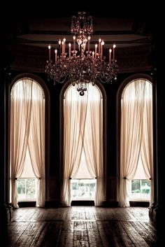 Gorgeous arched windows with pink sheers and a soft pink chandelier in a vacant apartment with a Parisian flair. #secretsinlace style