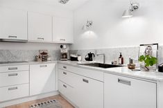 Meubles de cuisine blanc mat / plan de travail et crédence en marbre / Appliques en inox poli