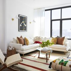 Mindy Kaling's New York City Living Room, striped rug, wood floor, white sectional, black window mullions, white paint color, accent pillows, ottoman