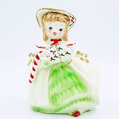 The girl has long eyelashes, a heart shaped mouth and is carrying a stack of Christmas presents with a red and white stripped candy cane over one arm. She is dressed in a cape and bonnet with mistletoe decorations and a green ruffled dress or skirt peeks out from underneath her cloak. | eBay!