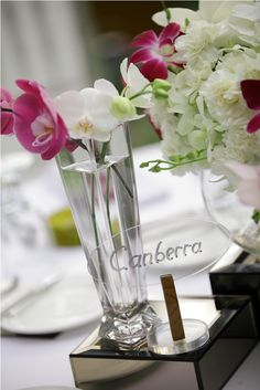 Orchid and Carnation flower centerpiece with table's name by Tirtha Bridal Uluwatu Bali Table Names, Flower Centerpieces, Calla Lily, Carnations, White Roses, Orchids, Bali, Glass Vase, Exotic