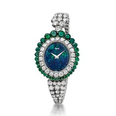 High jewellery wristwatch in white gold set with 88 diamonds and 32 emeralds. Opal dial.  Piaget ultra-thin quartz mouvement 7P.  Date: 1976