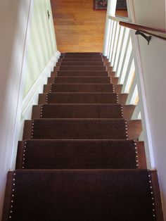 Stylin' DIY carpet runner for < $100: $5 area rugs from Ikea (just the right size to cover 2 stairs with no waste!), double-stick carpet tape to secure to the top of the stairs, a staple gun to secure under the lip of the stair, and upholstery tacks along the edge to add flair and secure the edges. Less than a day to complete (the tacks -- 22 on each stair -- took the most time).