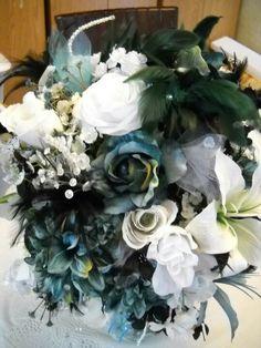 Closeup of white, black & teal flower arrangements
