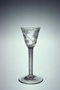 """Jacobite Drinking Glass. Hand-Blown & Engraved Glass. Circa 1750. 13.75cm x 5.1cm x 6.5cm. Engraved with a Blooming Rose, a Rose Bud, Leaves and Inscribed """"Redeat"""" (May He Come Back). Corning Museum of Glass"""