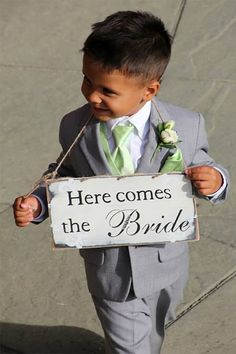 Cute rustic-type sign for ring bearer instead of a ringbearer pillow. Looks like they used natural twine to hang around his neck. #MyOnlineWeddingHelp