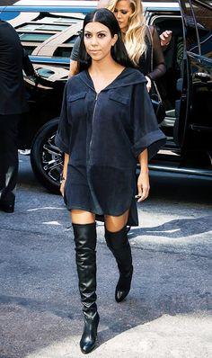 Kourtney Kardashian wears a navy tunic dress with black over-the-knee boots.