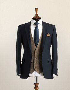 Wedding Suit Hire A mannequin wearing a navy lounge suit jacket with brown check waistcoat and patterned blue tie.A mannequin wearing a navy lounge suit jacket with brown check waistcoat and patterned blue tie. Wedding Suit Hire, Wedding Men, Tweed Wedding Suits, Mens Wedding Style, Brown Suit Wedding, Vintage Wedding Suits, Wedding Ideas, Mens Fashion Suits, Mens Suits