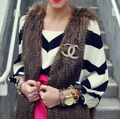 Chanel brooch on fur vest paired with a black and white chevron blouse.