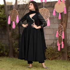 This angrakha suit set brings a twist to the classic black dress with its wrap top like top half. The simple but chic plain, black angrakha top is brightened by wide golden borders that end in tasseled strings that tie up elegantly Kurta Designs, Simple Kurti Designs, Kurti Designs Party Wear, Blouse Designs, Dress Indian Style, Indian Fashion Dresses, Indian Designer Outfits, Indian Outfits, Stylish Dresses For Girls