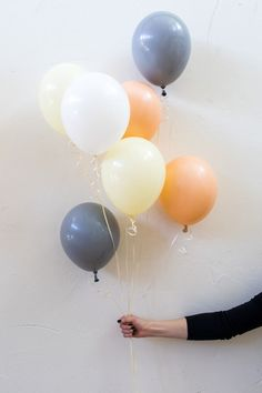 Orange, yellow, white and blue-gray colors create a cohesive color palate for this balloon design. These colors create a bright and light feel that is balanced by the darkness of the blue-gray balloons.