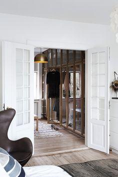 To fløjdøre forbinder soveværelset med et walk-in-closet, der er bygget af Københavns Møbelsnedkeri. Glasruderne giver en lethed i rummet, men kræver også, at parret holder orden. Loftlampen er også fra Københavns Møbelsnedkeri.