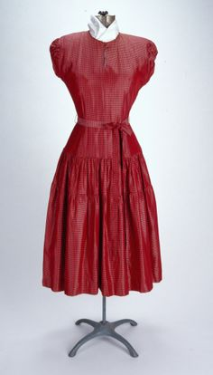 Red And Black Checked Taffeta Dress Made by Doris Dodson. (1947) Misses (junior sized) checked rayon taffeta day dress with tiny red & black checks. Mid- calf length, with full 3 tier skirt, padded shoulders, gathered puff cap sleeves. Split seam neckline opening with self covered button at throat/neck. Machine sewn. Missouri History Museum collections.