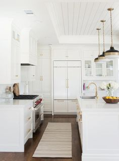 White kitchen features white shaker cabinets paired with white marble like countertops in Cambria Torquay Quartz and a white subway tile backsplash finished with white grout.